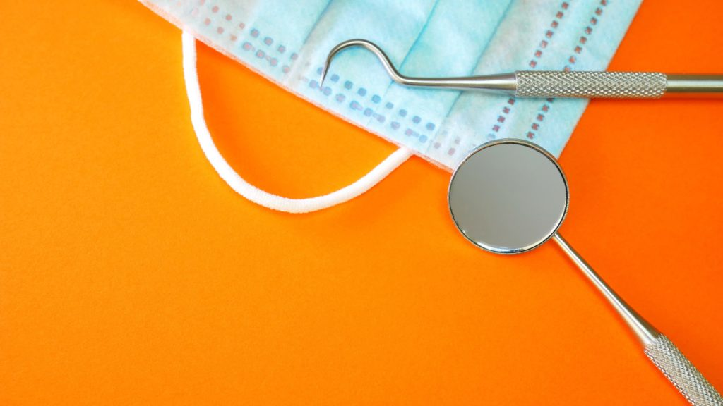 Dental tools with a mask laying on an orange background
