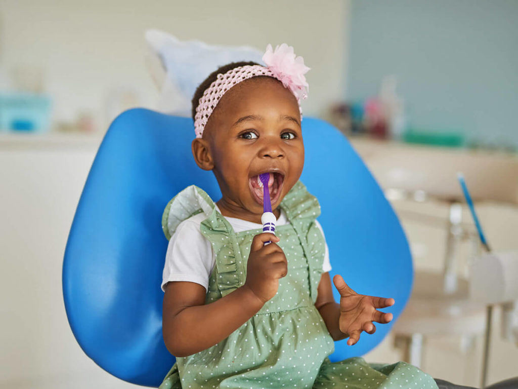 a child with a toothbrush in their mouth, at a pediatric dentist office