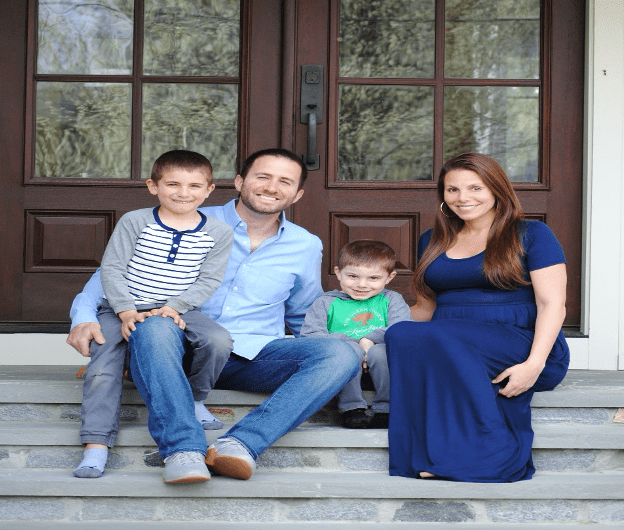 Dr. Markowitz and his family posing on the front steps of a house