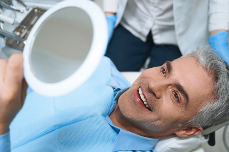A male dental patient laying back in a dental chair holds a mirror above his head and is smiling as he checks his teeth